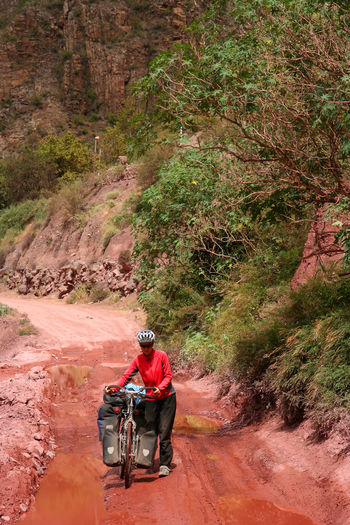 Woman with bicycle on dirt road against trees