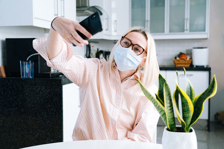 Woman wearing mask talking on video call at home