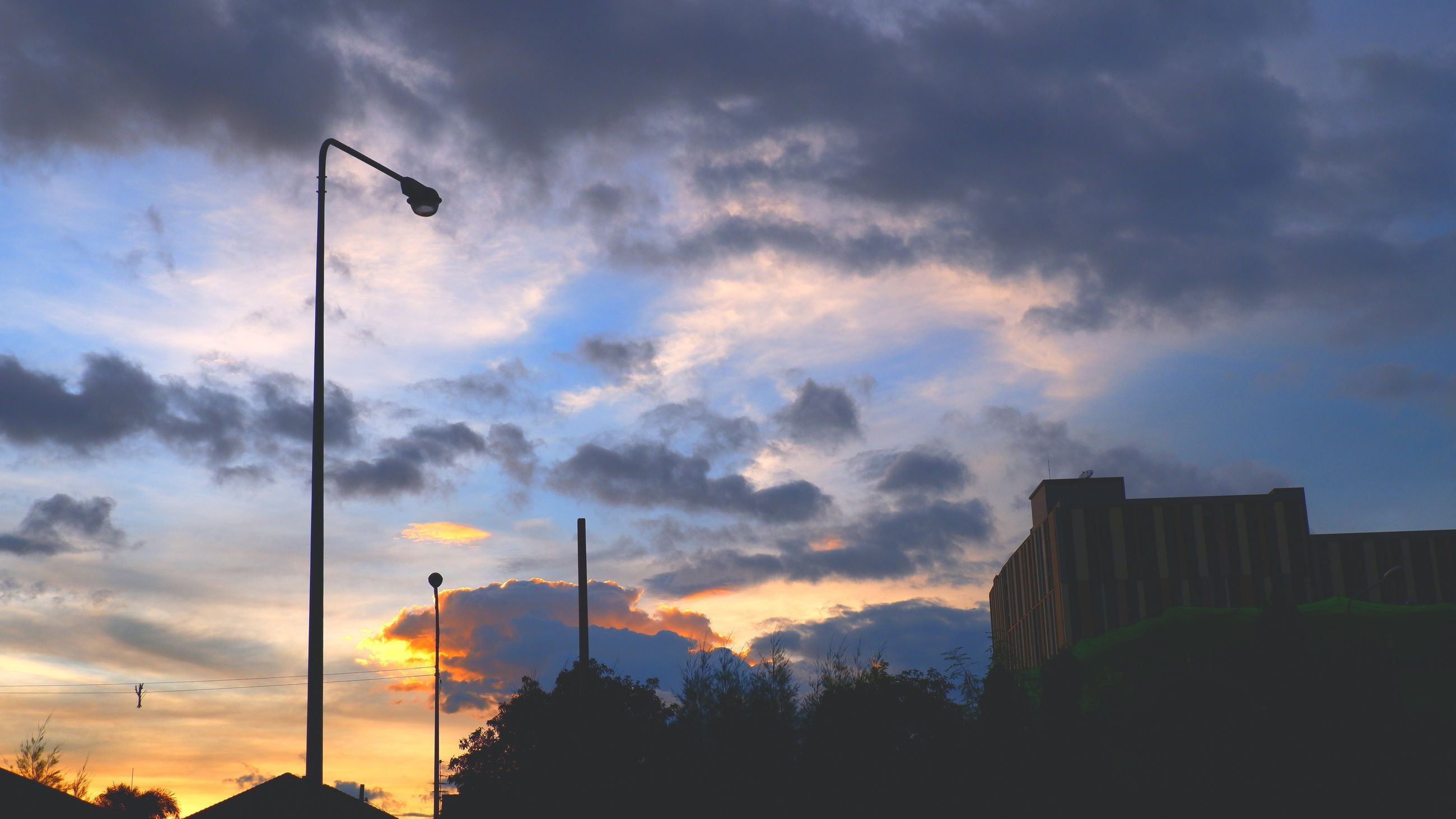 sky, cloud, sunset, dusk, evening, architecture, nature, sunlight, street light, built structure, silhouette, horizon, building exterior, city, afterglow, sun, street, no people, beauty in nature, outdoors, dramatic sky, tree, building, lighting equipment, environment, skyline, scenics - nature, low angle view