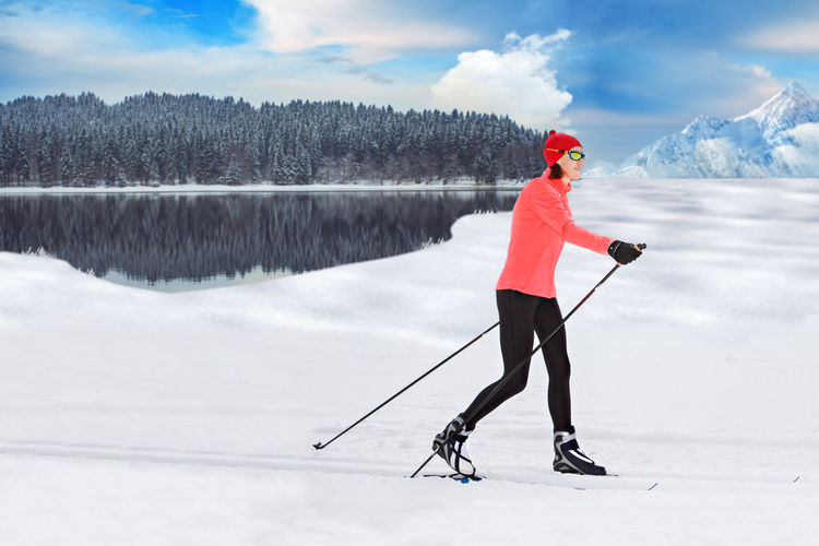 A woman cross-country skiing in the Alps Action, Activity, Adult, Competition, Cross-country, Female, Fit, Fitness, Forest, Healthy, Holidays, Langlauf, Lifestyles, Nordic, People, Running, Skating, Skiing, Snow, Sports, Style, Training, Winter, Woman Beauty In Nature Cloud - Sky Cold Temperature Day Full Length Ice Lake Leisure Activity Lifestyles Nature One Person Real People Scenics - Nature Sky Snow Sport Warm Clothing Winter Winter Sport