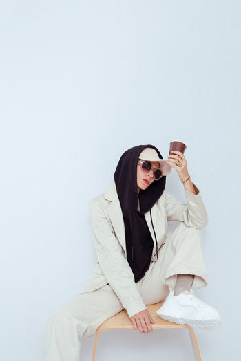 Young woman wearing sunglasses sitting on table against white background