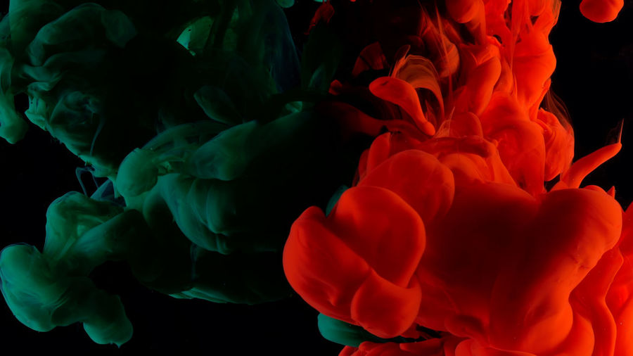 Close-up of red and green liquid over black background