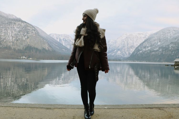 Full length of woman standing by lake against mountain during winter