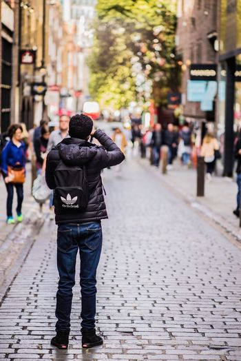 Rear View Street Photography Themes Real People Men Walking Photographing Focus On Foreground Full Length Outdoors One Person Day Camera - Photographic Equipment City Architecture Adult One Man Only People Adults Only The Week On EyeEm Postcode Postcards