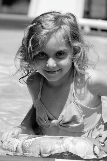 One of my younger sisters 💜 Kids Of EyeEm Black And White Happy Child  Hot Summer Days Blonde Curly Hair Water Pool A Swimming Kind Of Day Cute Bathing Suit Eyeem Photography Inner Tube Water Droplets Cooling Off In The Heat