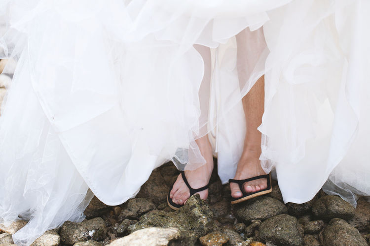 Low Section Of Woman In Wedding Dress Wearing Flip-Flops