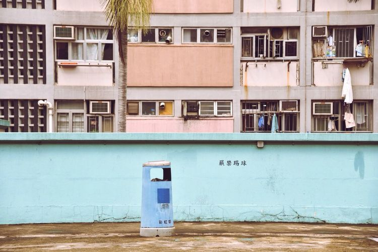 Garbage can on street against buildings