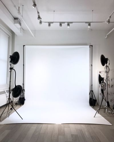 White Backdrop With Lighting Equipment On Floor At Studio