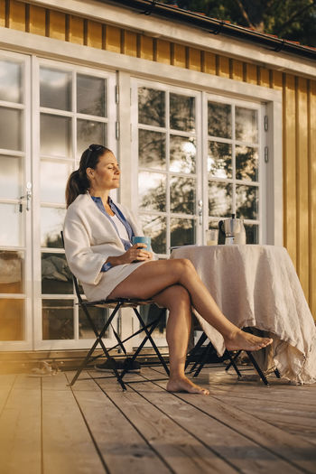 Side view of woman sitting on chair