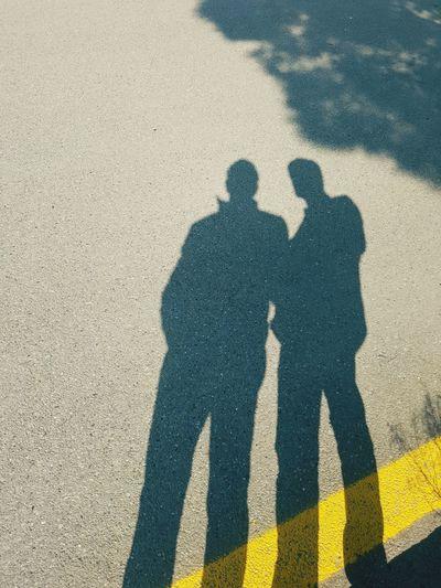 Shadow of men on road