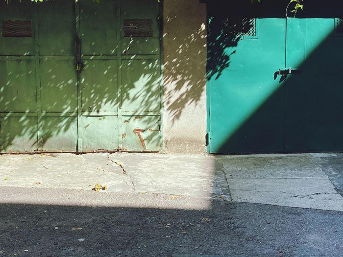 Shadow of birds on wall by footpath