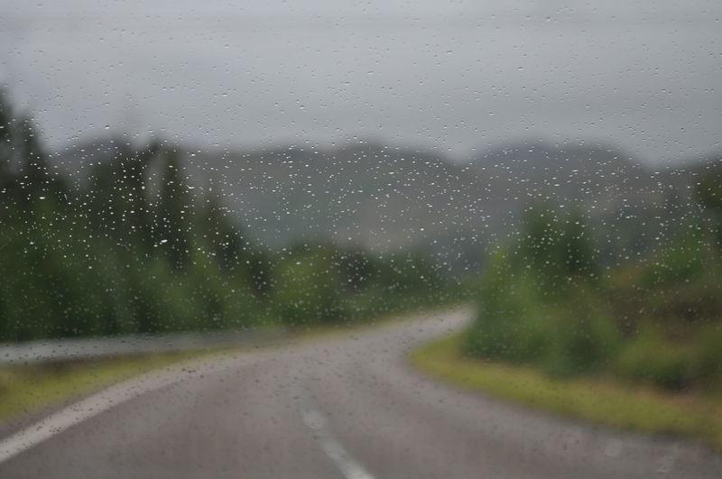 Road seen through wet window in rainy season