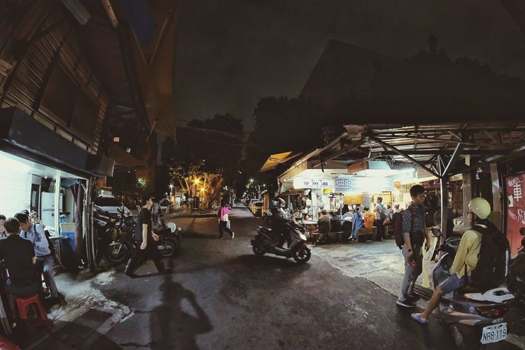 People on street against illuminated city at night