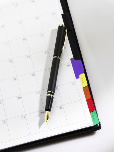 High angle view of pen with diary on table