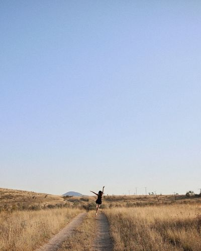 Rear view of woman on dirt road amidst grassy landscape against clear sky