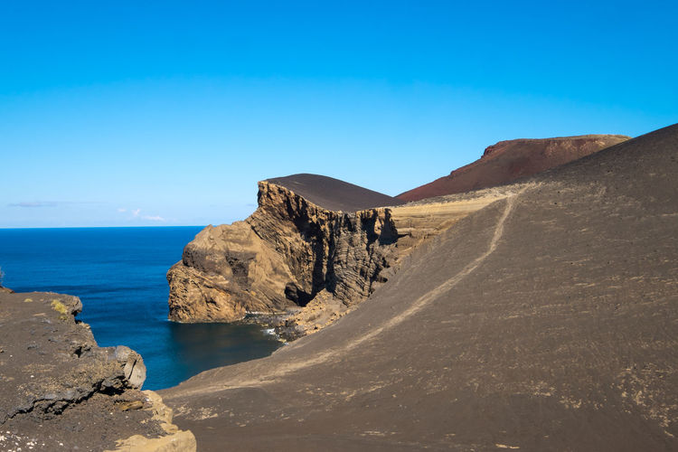 Volcanic lanscape in Faial Island, Azores, Portugal Arid Climate Azores Beauty In Nature Blue Clear Sky Day Faial Geology Landscape Mountain Nature No People Non-urban Scene Outdoors Physical Geography Rock - Object Rock Formation Scenics Sea Sky Tranquil Scene Tranquility Volcanic Landscape Water