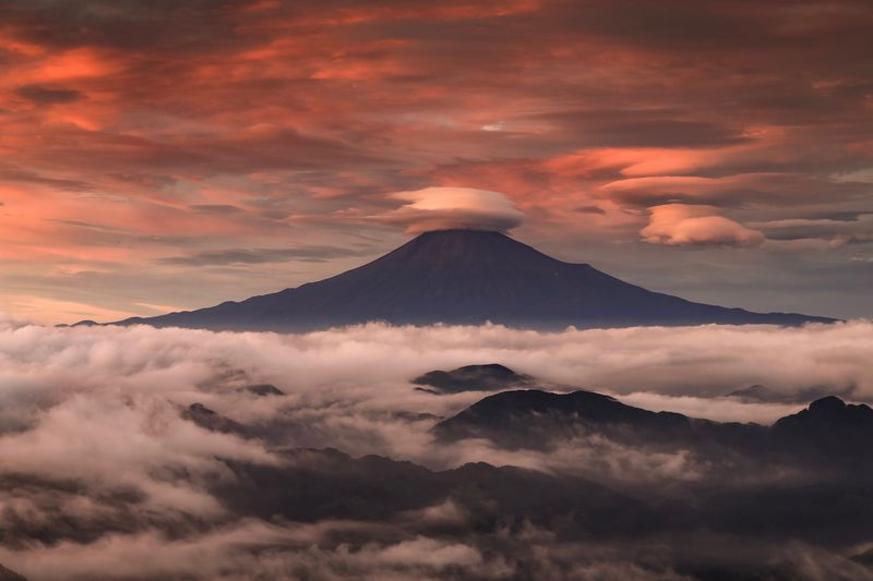 Majestic view of volcanic mountain against cloudy sky during sunset