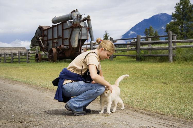 young woman with a cat - in a rural scenery Agriculture Animal Themes Canada Casual Clothing Cat Cat Lovers Cats Cat♡ Crawling Domestic Animals Farm Field Full Length One Animal One Woman Only One Young Woman Only Outdoors Pet Pet Owner Pets Real People Rural Scene Woman Young Woman Young Women