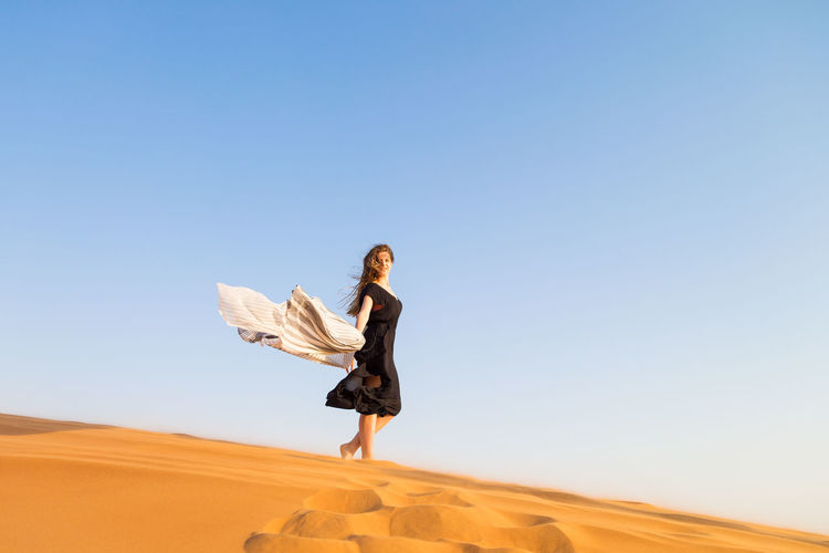 Full length of woman standing on sand dune against clear sky