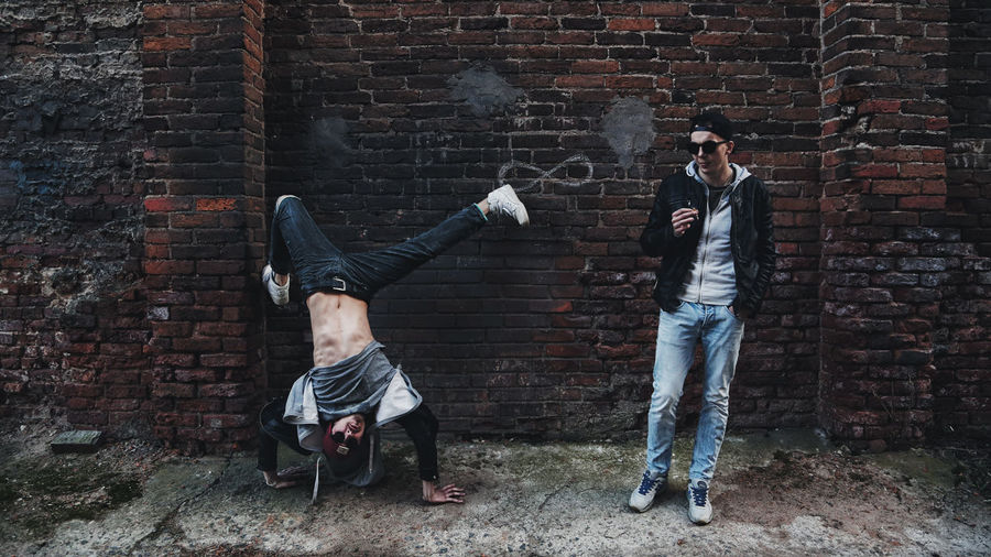 Hipster Men Against Brick Wall