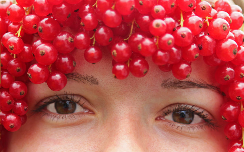 Close-Up Portrait Of Young Woman With Red Currants On Head
