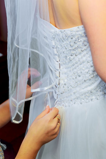 Cropped Hands Of Beautician Dressing Bride During Wedding