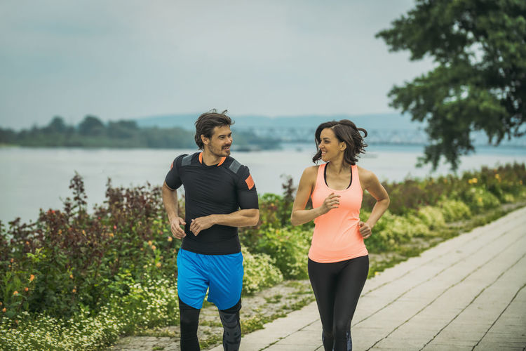 Smiling male and female athletes jogging on footpath