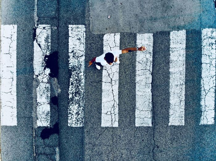 Directly Above Shot Of Man Standing On Zebra Crossing In City