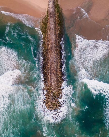 Aerial view of a majestic breakwater with rough rolling water waves rolling, setubal, portugal.