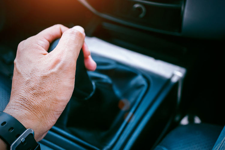 Midsection of person holding cigarette on car