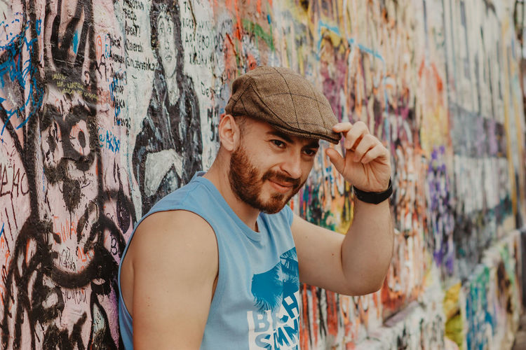 Young man looking away while standing against graffiti wall