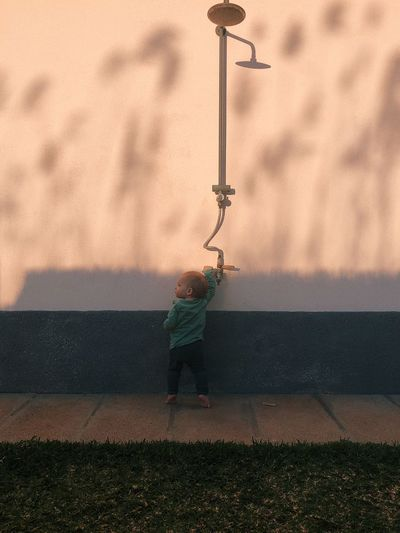 Boy standing by wall against sky