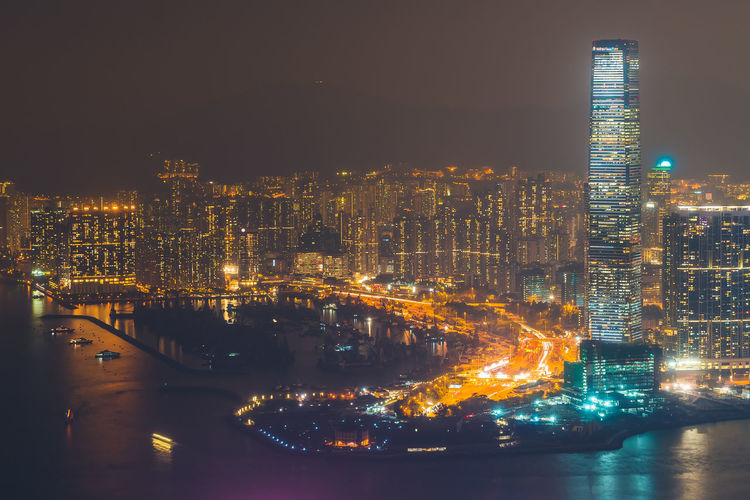 Illuminated Buildings At Victoria Harbour In City During Night