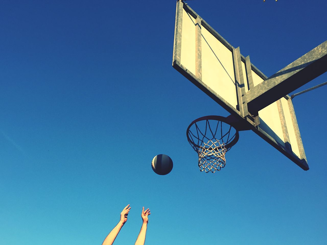 sky, basketball - sport, sport, blue, low angle view, basketball hoop, ball, clear sky, nature, copy space, day, playing, net - sports equipment, leisure activity, people, mid-air, motion, outdoors, sunlight, human body part, basketball - ball, human limb, arms raised, finger