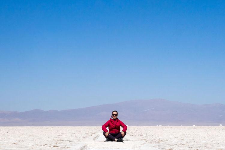 Full length of man sitting on land against clear blue sky