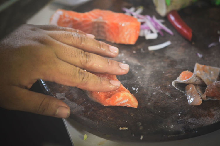 Finger Focus On Foreground Food Food And Drink Freshness Hand Healthy Eating Holding Human Body Part Human Hand Indoors  Kitchen Lifestyles Meat One Person Preparation  Preparing Food Real People Salmon Unrecognizable Person Wellbeing
