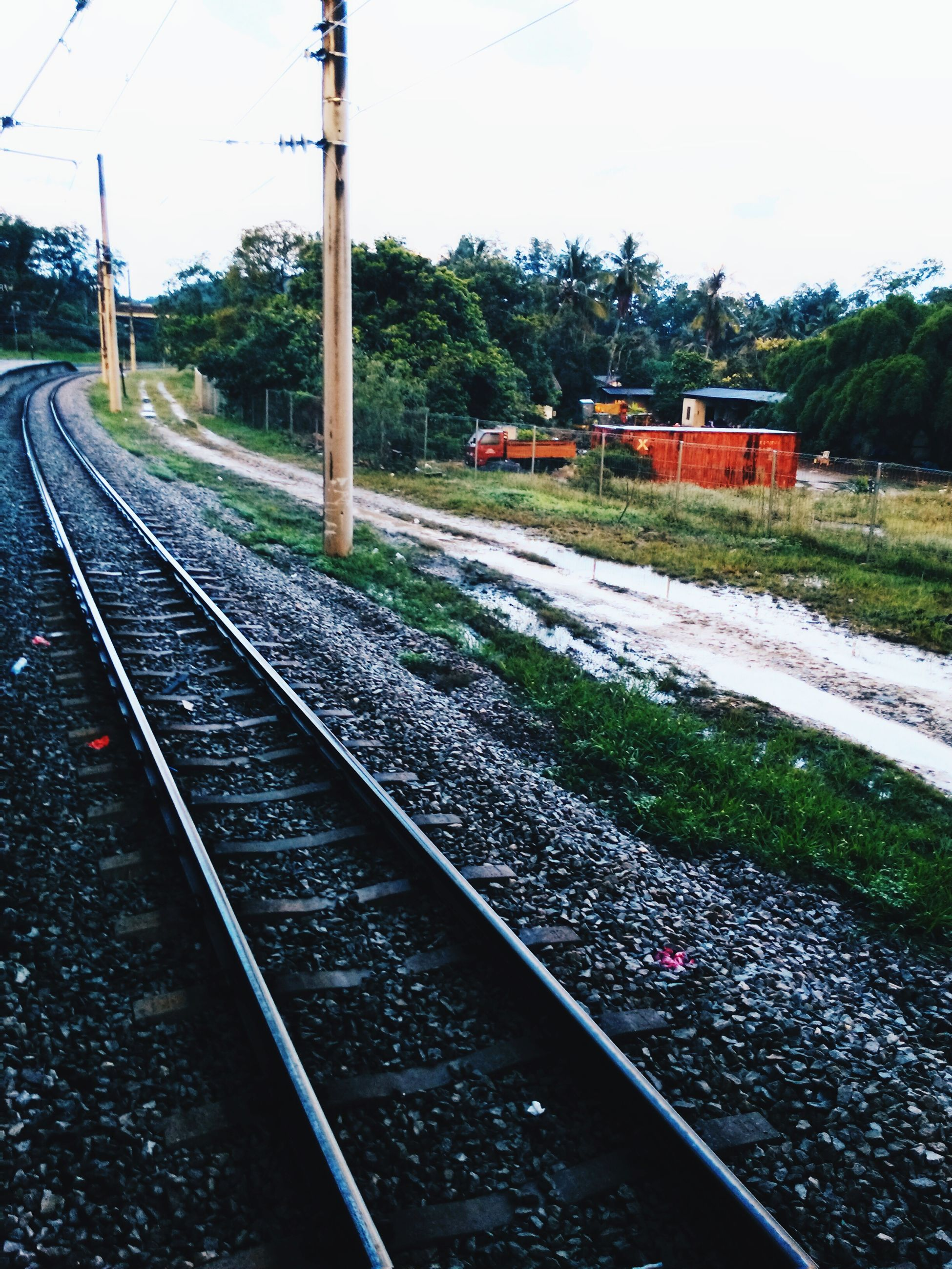 railroad track, transportation, rail transportation, public transportation, railroad station platform, train - vehicle, railway track, railroad station, mode of transport, tree, train, travel, high angle view, clear sky, diminishing perspective, vanishing point, passenger train, the way forward, power line, day