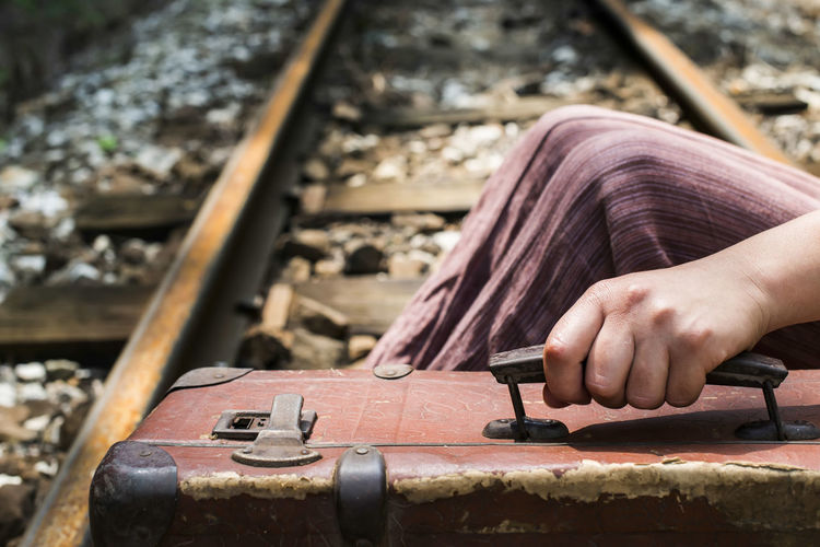Midsection of woman holding suitcase while sitting on railroad track