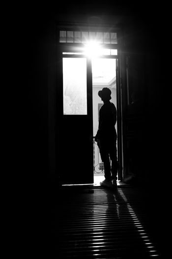 Silhouette man standing at entrance of building