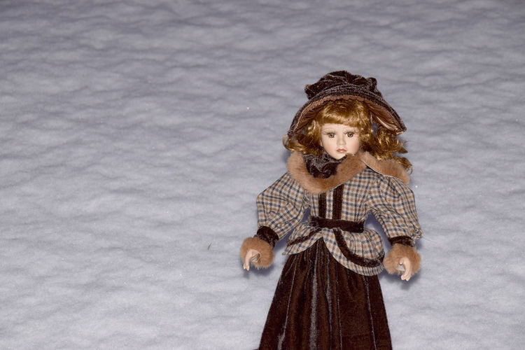 cute and beautiful Old porcelain doll on snow background One Person Looking At Camera Clothing Front View Portrait Winter Standing Cold Temperature Young Adult Warm Clothing Women Smiling Brown Hair Lifestyles Snow Hairstyle Porcelain  Porcelain Doll Copy Space Beautiful Dress  Collection Cute Toy Model Dress