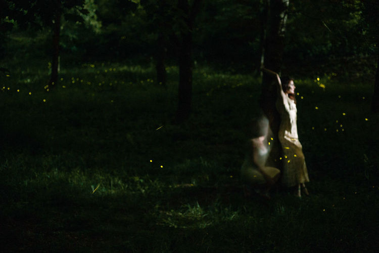Woman on field by trees at night