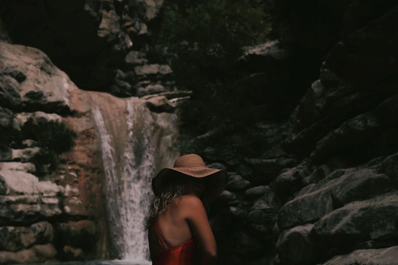 Side view of woman standing against waterfall