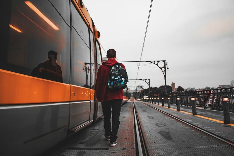 Rear view of young man with backpack standing on street against sky