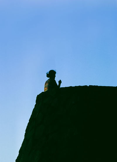 Low angle view of silhouette person on rock against clear blue sky