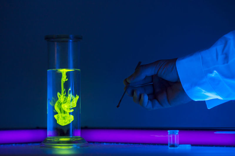 Cropped hand of scientist by container with liquid on table