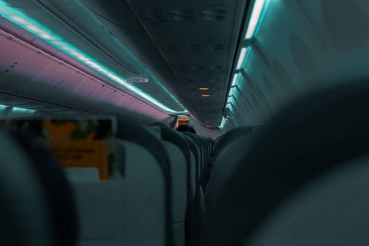 Air Vehicle Airplane Airport Architecture Diminishing Perspective Exit Illuminated Indoors  Journey Land Vehicle Lifestyles Light Mode Of Transportation Passenger Public Transportation Real People Seat Train Train - Vehicle Transportation Travel Vehicle Interior Vehicle Seat
