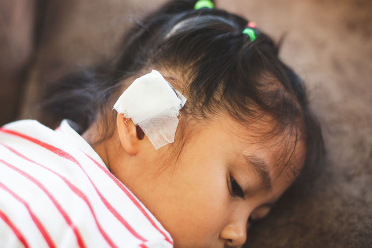 Close-Up Of Girl With Bandage On Ear