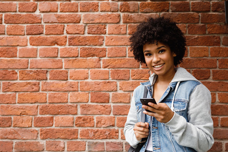Portrait of smiling young woman using mobile phone against brick wall