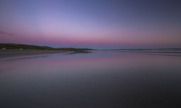 Colourful twilight sky over sandy beach at low tide in Newgale, Pembrokeshire, UK Newgale Twilight Wales Beach Beauty In Nature Cloud - Sky Coast Idyllic Land Nature No People Non-urban Scene Outdoors Pembrokeshire Purple Reflection Scenics - Nature Sea Sky Summer Sunset Tranquil Scene Tranquility Uk Water