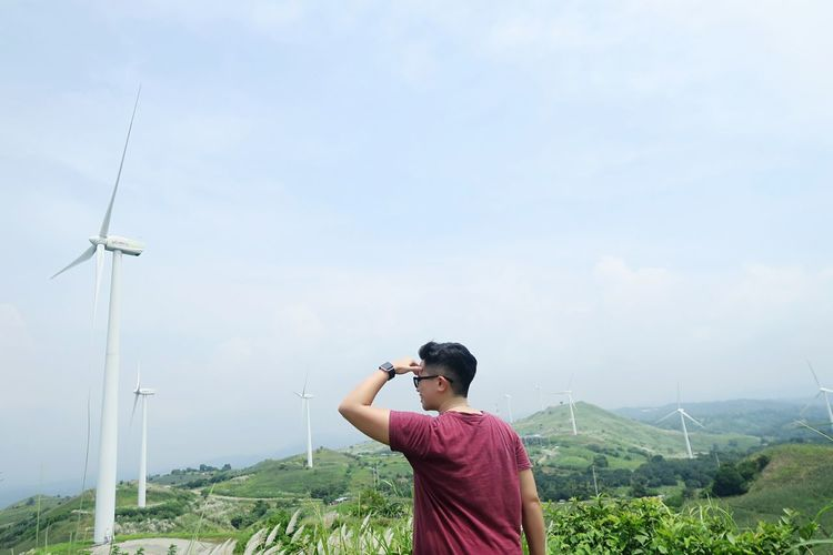 Man shielding eyes while looking away against windmills and sky on field